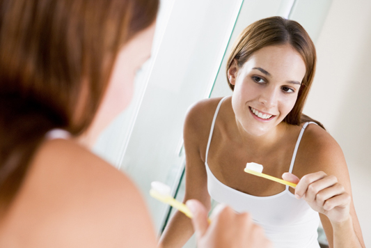 Woman in bathroom brushing teeth and smiling